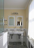 Traditional bathroom with vintage-style pedestal sinks against pastel yellow wall and integrated cabinet with mirrored door