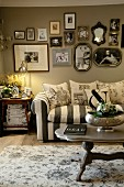 Striped couch with scatter cushions below gallery of photos on pale grey wall in vintage-style living room