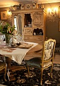 Antique chair with gilt wooden frame and vintage printed upholstery at table in front of wooden cabinet with mirrored door