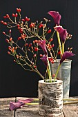 Rose hips and calla lilies in vases on wooden table