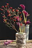Hagebutten und Calla in Vasen auf Holztisch