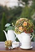 Porzellankannen und festlicher Blumenstrauss aus apricotfarbenen Rosen und Hortensien