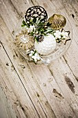 Vintage Christmas decorations and snowberries on glass cake stand on wooden table
