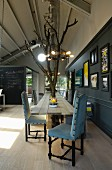 Long, pale wooden dining table with integrated tree trunks, chairs upholstered in pale blue in loft-style interior