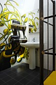 Mural of climbing plant on white tiles and pedestal sink in bathroom