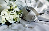 White bridal shoes and jewellery lying next to bouquet of white roses on satin fabric