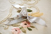 Vintage cutlery with cream plastic handles tied with ribbon on embroidered tablecloth