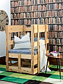 Hand-crafted rustic chair with seat cushion and scatter cushions against photo mural of bookcase