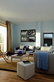 Various seating, pale pouffe and armchairs in background below collection of pictures on living-room wall painted pale blue