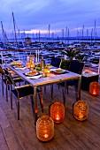 Bodenlaternen mit Kerzenlicht vor gedecktem Esstisch auf Terrasse, im Hintergrund Yachthafen in Abendstimmung