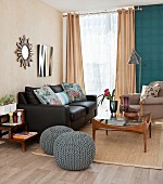Black leather couch, retro glass coffee table and blue-grey crocheted pouffes in living room
