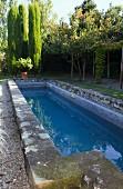 Lang gestreckter Pool mit verwitterter Steineinfassung in mediterranem Garten