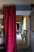 Red brocade curtain hanging in doorway with view of vintage wooden chair against yellow-painted wall