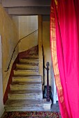 Vintage stairwell with masonry winding stairs, delicate handrail and hot pink curtain in foreground
