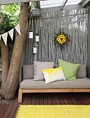Wooden bench with seat cushion and scatter cushions on roofed terrace