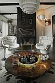 Runder edler Glastisch mit abgesenkter Hausbar, weisse Retro-Ledersessel vor künstlerisch gestaltetem offenem Metall-Kamin