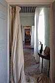 Blick durch offene Tür mit bodenlangem Vorhang auf zierlichen Wandtisch und Vintage-Steinboden