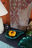 Yellow pepper in turquoise ceramic dish in front of vintage wooden board