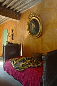 Pink quilt on antique sleigh bed below family portrait in oval, gilt frame on ochre wall