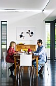 Man and woman at wooden breakfast table on modern white chairs in contemporary interior