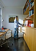 Man in narrow study with classic office chair at desk and fitted wooden cupboards