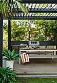 Table and benches on modern terrace below slatted pergola