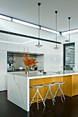 Kücheninsel mit weisser Arbeitsplatte und Holzfront, Barhocker und Klassiker Pendelleuchten
