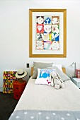 Scatter cushions and cloth rabbit on child's bed below framed picture