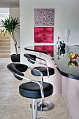 Breakfast bar with curved granite top and two black leather and chrome bar stools