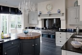 Free-standing kitchen counter with integrated, round, walnut butchers' block in country-house kitchen