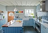 Landhausküche mit hellblauen Fronten, Mittelblock mit Arbeitsplatte aus Marmor und Walnussholz