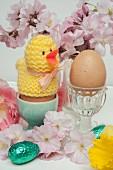 Osterstillleben mit Frühstückseiern in Eierbecher und Kirschblüten