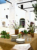 Ochre tablecloth, crockery and vases of Mediterranean flowers on table under pergola outdoors