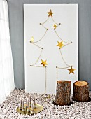 Hand-crafted stylised Christmas tree made from gold chain, stars and white plywood board behind tree stump stools and candles