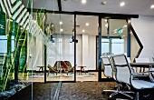 Classic office chairs in modern office in front of open door in steel and glass wall with view into lounge area