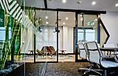 Klassiker Bürostühle in modernem Büro, im Hintergrund Stahl-Glaswand mit offener Tür und Blick in Loungebereich