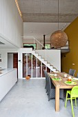 Wicker chairs and green highchair at wooden table: staircase and gallery in background in contemporary loft apartment