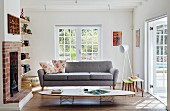 Classic coffee table in front of grey couch and open fireplace in living room