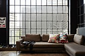 Modern corner couch in front of industrial window