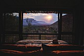 Romantic view of sunset over wild landscape seen from bed through panoramic window