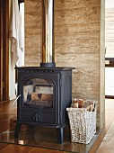 Cast iron stove and basket of logs on glass panel against wall