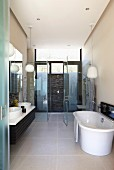 Free-standing bathtub on large floor tiles in front of glazed shower area in modern bathroom