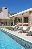 Sun loungers with grey mattresses next to pool adjoining white bungalow with spacious loggia