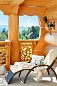 Moderne Outdoor Liege mit weißem Polster auf Balkon eines Blockhauses, Ausblick in idyllische Landschaft