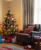 Decorated Christmas tree and presents next to brown armchair in corner of living room