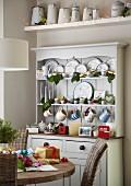 Esstisch mit Weihnachtsgeschenken, im Hintergrund Anrichte in ländlichem Stil mit Geschirr