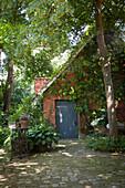 Bewachsenes Backsteinhaus im idyllischen Garten