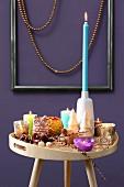 Tabletttisch mit bunter Kerzendeko vor lila Wand