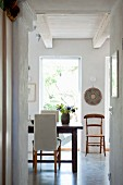 Dining area with pale upholstered chairs and wooden chair between French windows in background