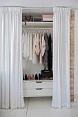 Offene, bodenlange weiße Vorhänge vor Kleiderschrank mit Blick auf Damenkleidung